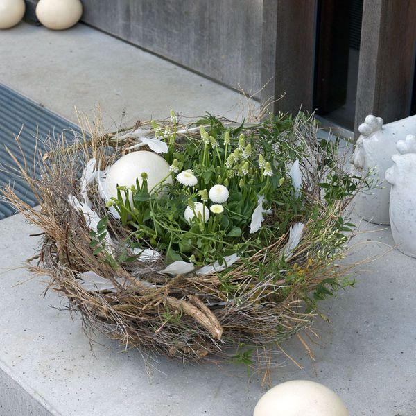 Osterdeko: Osternest mit Frühlingsblumen in Weiß