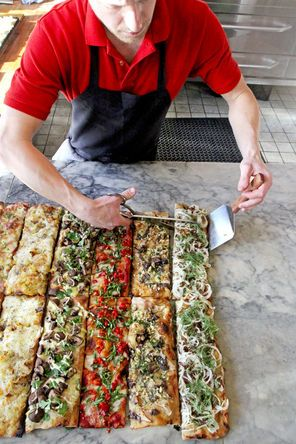 Best new cheap eats for 2015.  Johannes Heitzeberg cuts slices of the Roman-style pizza at Pizzeria Gabbiano in Seattle's Pioneer Square.