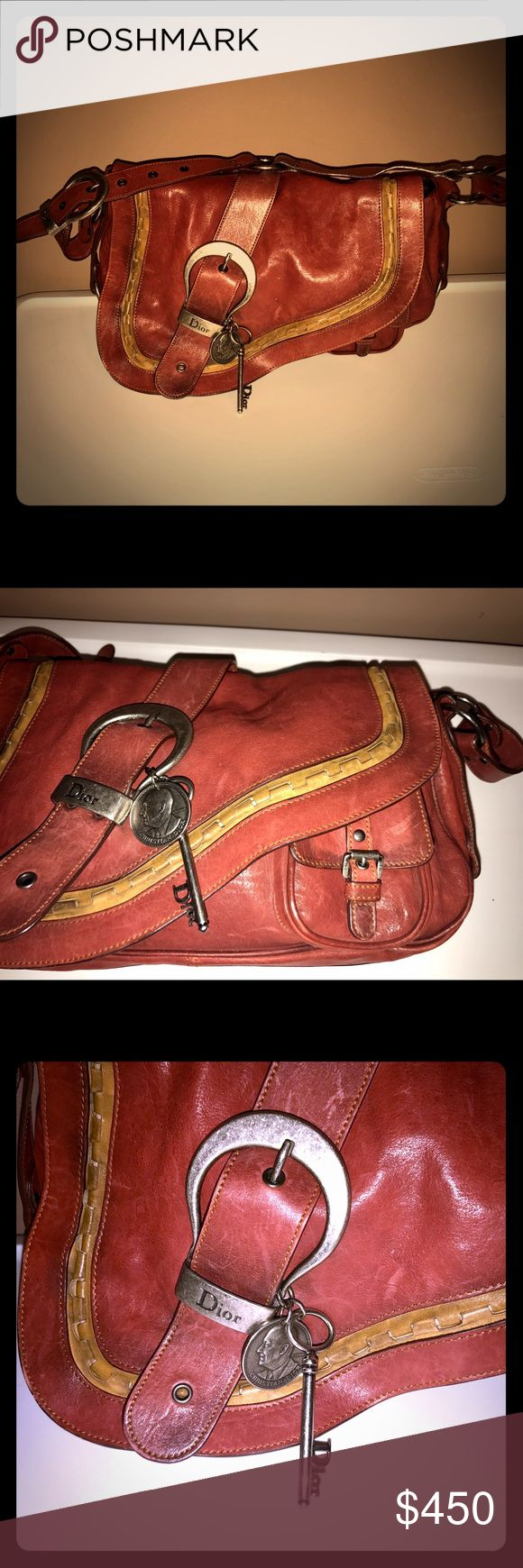 "DIOR Gaucho Belt Buckle Key Charm Saddle Bag Excellent preowned condition. Rustic. Smooth light brown distressed leather Gaucho shoulder bag by DIOR. Tan stitching and saddle flap with tan leather piping, belt detail with silver tone tarnished buckle embellished with ""Dior"" key and coin charms, mini front pocket, and belt buckle shoulder strap with loop hardware. Logo interior pristine clean. Made in Italy.  Length: 15 in. Width: 3.5 in. Height: 9 in. Strap Drop: 10 in. Dior Bags Shoulder…"