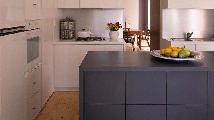 Кухонный остров контрастного серого цвета служит дополнительной поверхностью на кухне. .