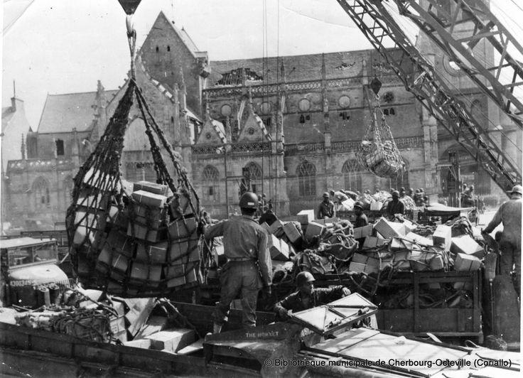 """https://flic.kr/p/edf3Vg   CHBG_2GM_012   Cherbourg, place Napoléon devant la basilique Sainte Trinité au point de transfert N°1 des troupes """" colored """" de compagnies Amphibious Truck déchargent des filets de manutention remplis de caisses et de cartons de matériels. Au premier plan un Dukw baptisé """" The Hornet """" à l'intérieur un sous-officier (trait horizontal à l'arrière du casque) d'autres vues: CHBG_2GM_012, CHBG_2GM_024,  2GM_CHBG049, 2GM_CHBG363 et 2GM_CHBG370 www.flick"""