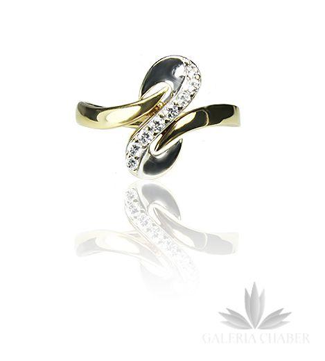 Ciekawy pierścionek wykonany ze złota próby 585. W wyrobie osadzono cyrkonie dodatkowo ozdobione wstawkami z białego złota. Wzór o szerokości około 1,5 cm na 0,6 cm.