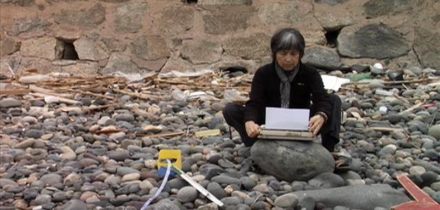 Cecilia Vicuña, escribiendo en la playa de Con Con.