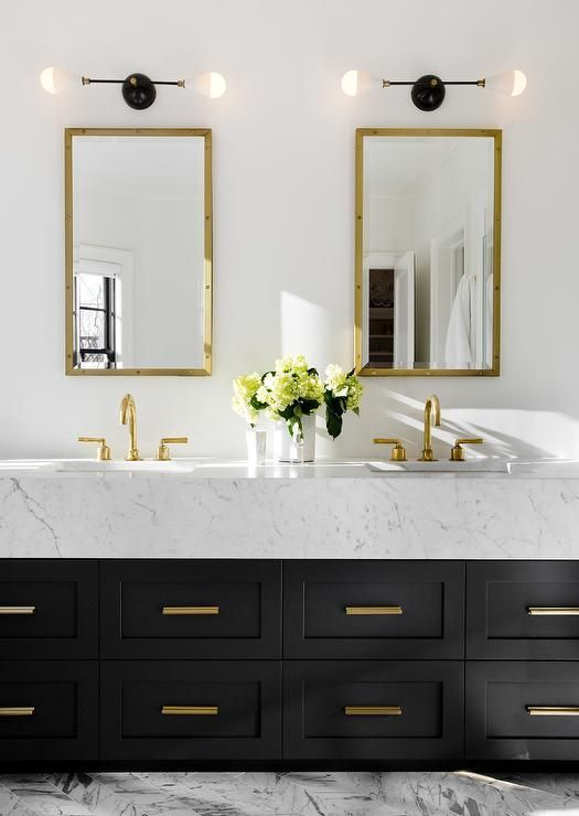 Stunning contemporary black, white and gold bathroom boasts white walls holding two mounted Rivet Medicine Cabinets in Antiqued Brass from Restoration Hardware hung above a black double washstand topped with thick white marble countertops fitted with polished brass gooseneck faucets and shaker cabinets finished with brass vanity pulls as gray and white marble herringbone floor tiles are illuminated by two black and white 2 light sconces.