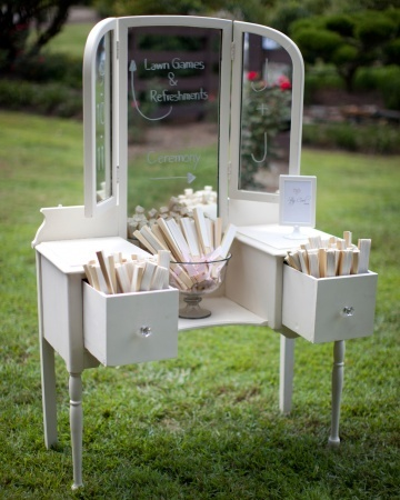 A vintage dressing table serves as a directional sign and holds fans for guests to use