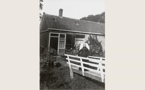 Vrouw uit Kortgene in Noord-Bevelandse streekdracht. Ze is gekleed in haar zondagse dracht of gelegenheidskleding. De vrouw draagt onder de sluiermuts een ondermuts met daarin een oorijzer. Aan de spiraalvormige gouden oorijzeruiteinden, de krullen, hangen gouden oorijzerhangers. 1918-1941 vanAgtmaal #Zeeland #NoordBeveland