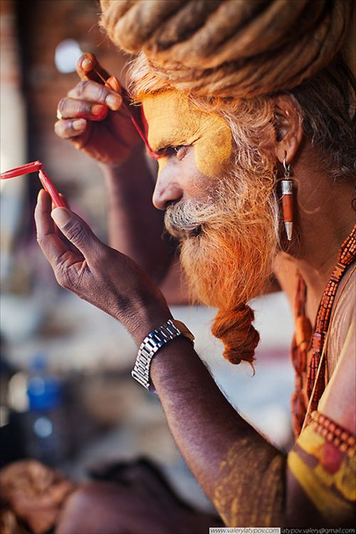 Of marks, faces and identities: A 'Sadhu' paints the mark of Lord Vishnu on his forehead, India