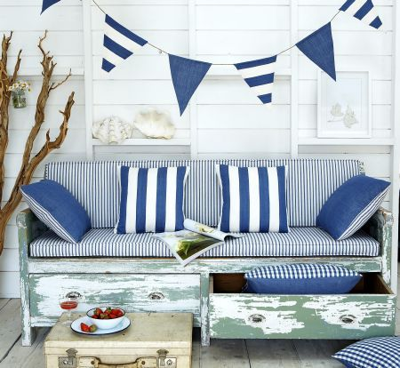 Prestigious Textiles -  Maritime Fabric Collection - Antique bench with blue and white striped seating pads, striped and chequered cushions and blue bunting for a maritime setting