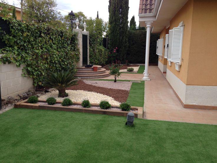 estupendo jardin sostenible y ejemplar que combina csped artificial con piedras decorativas de madera