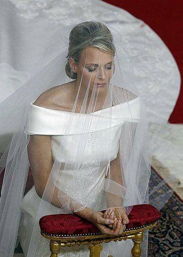 Charlene de Monaco lors de la bénédiction du mariage, son voile de tulle de soie devant le visage et derrière elle sa traîne brodée