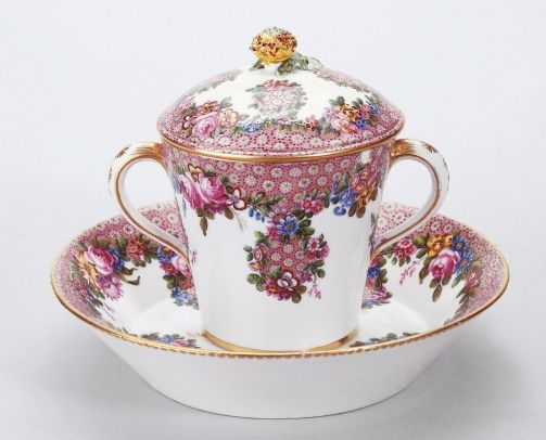 "1768 French Sèvres Cup and saucer in the Royal Collection, UK - From the curators' comments: ""Sèvres soft-paste porcelain covered cup and saucer. White ground painted in polychrome with floral trails and a mosaic pattern. The cup, which is in the form of an inverted and truncated cone, is fitted with two white and gold handles and a domed cover crowned by a carnation-and-leaf knob painted naturalistically. The deep saucer has angled sides."""