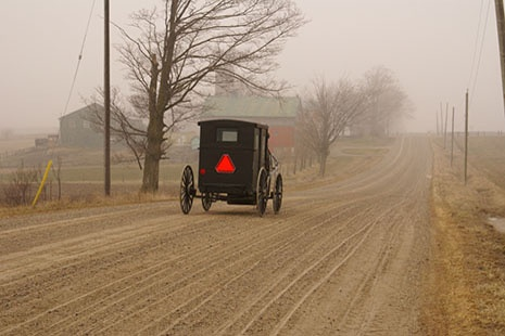 Mennonite carriage going along a dusty country road in Waterloo County, Ontario, Canada.
