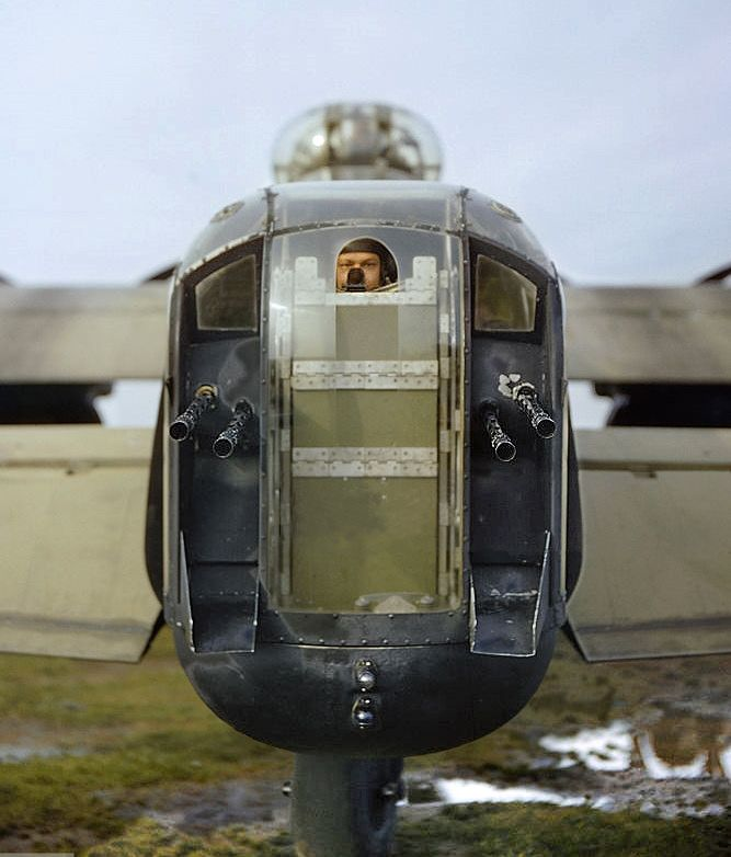 A gunner...believed to be Sgt J Bell...Looks through the opening in the perspex of the rear turret of R5740/ 'KM-O'.. The four .303 Browning machine guns could discharge at a combined rate of 7,000 rounds a minute but were outranged by the heavy calibre cannon of most Luftwaffe night fighters.