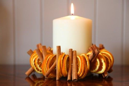 dried oranges and cinnamon sticks threaded and tied around a candle.
