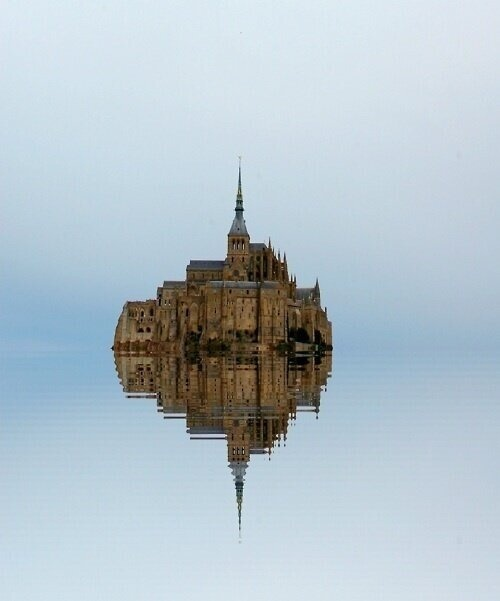 Mont Saint Michel completely surrounded by water , France.