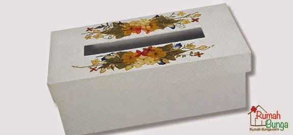 Kotak tisu dari board yang dilapis kertas putih bertekstur, dihias rangkaian bunga kering di atasnya.