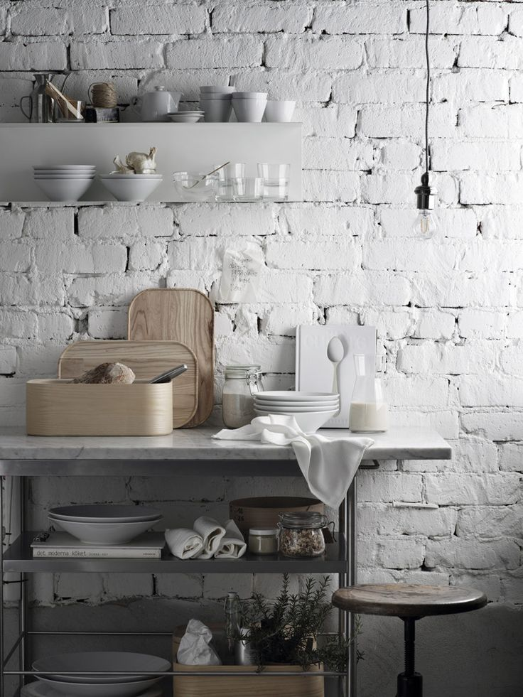 The white bricks contrast nicely against this calm, decorative kitchen ensemble.