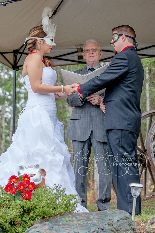 A glimpse of the bride and groom at their amazing outdoor, masquerade wedding. Wedding photography by Throughout Time Photography, #Quesnel, #British Columbia, #masquerade wedding, #autumn wedding, #masks, #bride, #groom, #wedding ceremony, #wedding dress, #wedding gown, #tux, #rain, #bridal mask, #red and white, #justice of the peace,