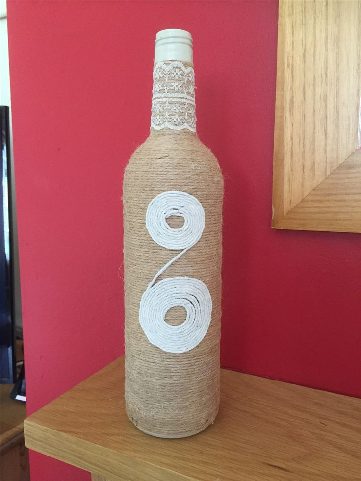 String covered wine bottle with lace and home made string pattern . Lovely