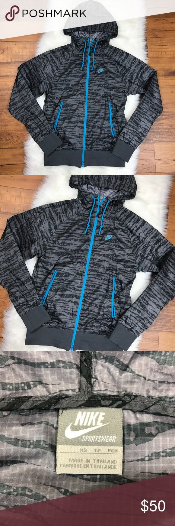 """Nike Windrunner Tiger Striped Lightweight Zip Up Nike Windrunner Tiger Striped Lightweight Windbreaker Zip Up. Very thin/lightweight. Gray/black tiger striped with blue trim details. Size XS. Armpit to armpit is about 17"""". Armpit to end of sleeve is about 21"""". The length of the jacket is about 24.5"""". Nike Jackets & Coats Windbreakers"""
