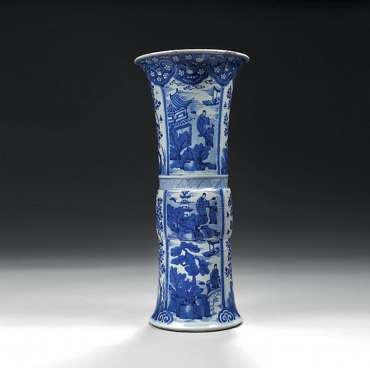 """CHINE - Époque KANGXI (1662-1722)  Important vase de forme """"Gu"""" en porcelaine décorée en bleu sous couverte de quatre médaillons de personnages dans des paysages lacustres animés et branches fleuries de pivoines émanant de rochers percés alternés. Le bord orné d'une frise de têtes de ruyi avec oiseaux et fleurs en réserves. Hauteur : 55,3 cm  Égrenures Provenance : Antiquaire Giroux - Bruxelles, le 3 septembre 1951  CHINA - KANGXI Period (1662-1722)  A blue and white """"Gu"""" vase."""