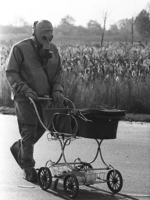 A Chernobyl Liquidator pushes an abandoned infant found while measuring radiation levels in a deserted village, 1986.