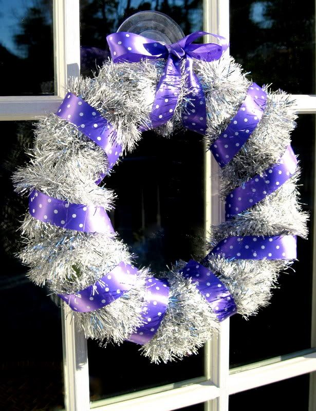 Quick DIY wreath from a wreath form, a tinsel garland, and some ribbon. Hang it on a window with a clear plastic suction hook.