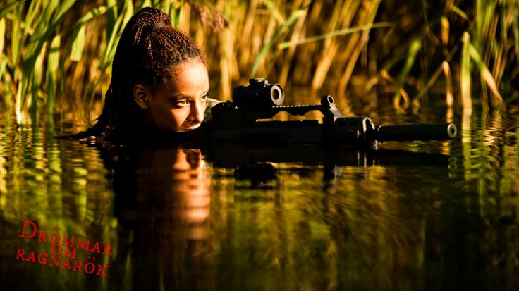 Woman in the water by the reeds. Carrying assault rifle with silencer.