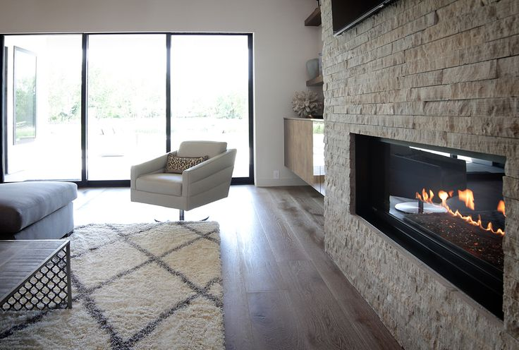 Renovare Model Home. The living room has a fireplace, backyard views of the Boise River and is open to the kitchen and dining areas for optimal entertaining.