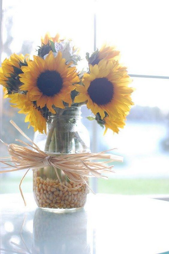 Sunflowers in corn kernals with corn husk bow for fall / http://www.himisspuff.com/country-sunflower-wedding-ideas/9/