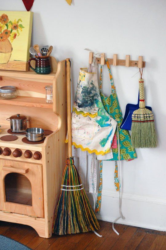 """Waldessori"" Playroom - I love many of the elements of this room, especially the hooks with the small aprons and natural brooms."