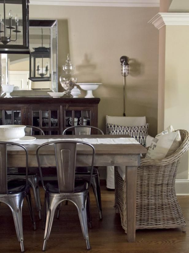a mix of rustic metal chairs with wicker dining chairs pulled together with a rustic farmhouse table buffet and lighting want those wicker chairs in my