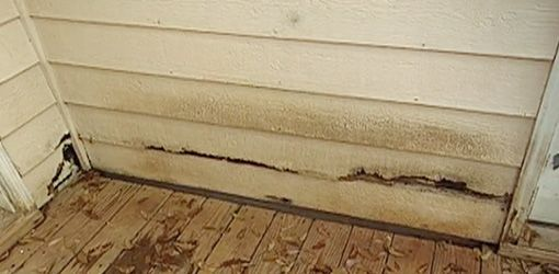 Rotten hardboard siding before replacement with fiber cement siding.