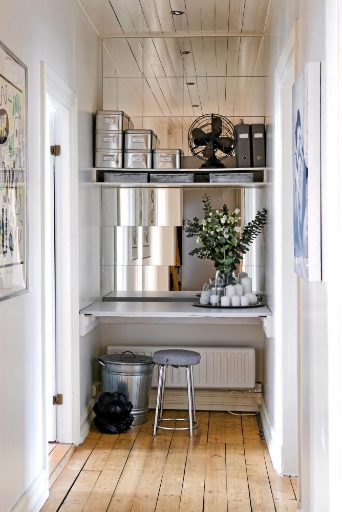 I entreen er plassen godt utnyttet, og beboeren har her valgt � lage en liten kontorplass i enden. Endeveggen er kledd med speil fra Ikea. Bokser fra Granit, og en gammel vifte har f�tt sin plass p� hyllen over skrivebordet. Krakken er arvet.