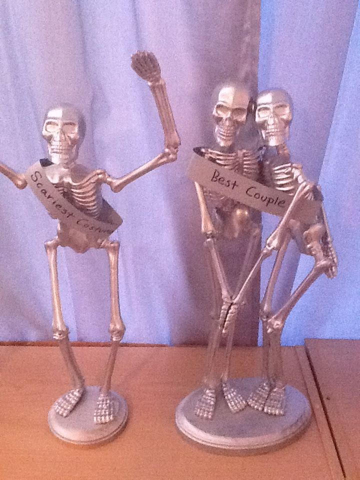 Skeletons from the dollar store mounted (hot glue) on round wooden block, spray painted and ready to be given out for awards during a Halloween party. You can dis-ensemble and hot glue back together in the shape or stance you desire.
