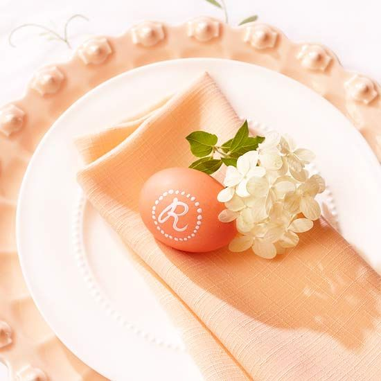 To achieve this sophisticated look, place a monogrammed egg with a sprig of white flowers on top of a colored napkin.