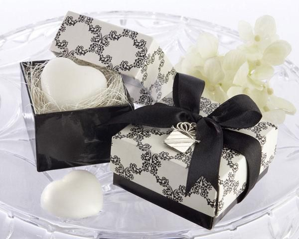Sweet Heart Soap Wedding Favor features a fresh scent. It is in the shape of a heart. It comes nestled atop natural raffia inside a gift box. This gift box has a black base with a cream and ivory damask cover. It is then wrapped in a black satin ribbon that is tied into a bow on top. The bow has a silver tone gift box charm.