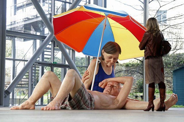 """A visitor looks at a sculpture entitled """"Couple Under an Umbrella, 2013"""" by artist Ron Mueck during the press day for his exhibition at the Fondation Cartier pour l'art contemporain in Paris April 15, 2013. (Photo by Charles Platiau/Reuters)"""