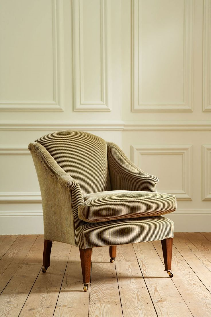 The Fielding chair is a compact and elegant armchair with scrolled arms and a high back. It has a separate seat cushion and tapered legs. Pictured here in Lucette, charcoal sand.