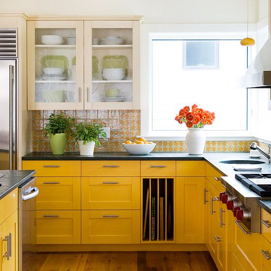 Sometimes backsplash tile can provide inspiration for the rest of the cooking space. Playful ceramic tile with yellow diamonds and green swirls inspired this kitchen's bold colors and cheerful mood. To match the tile's yellow hue, the base cabinets were painted mustard yellow. The warm off-white tone of the upper cabinets keeps the bold yellow hues from overpowering the room.