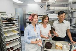 Smiling pastry chefs digital tablet in commercial kitchen