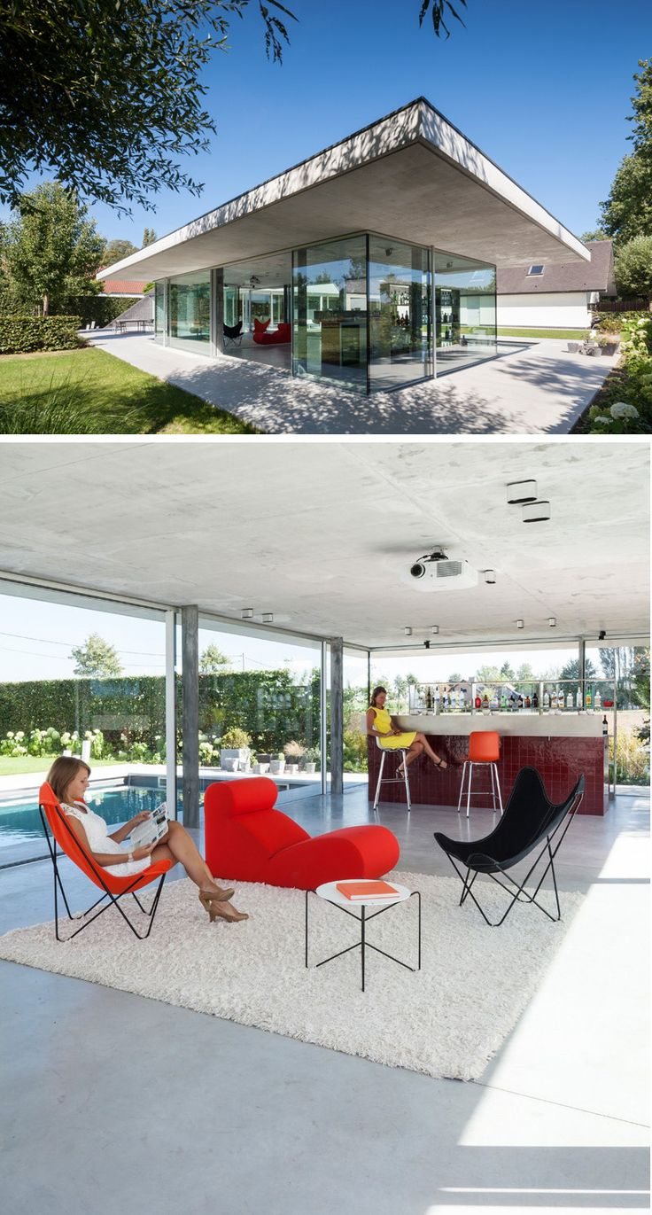 Surrounded by glass, this modern concrete pool house provides a great view of outside. A red tiled bar, and cozy seating make this a great place to have a drink after a dip in the pool.