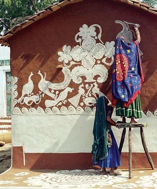 Meena women hand painting mud hut.