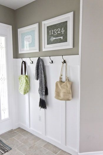 Front entry wainscoting with hooks; add extra lip at top for shelf to lean photo frames or canvas prints