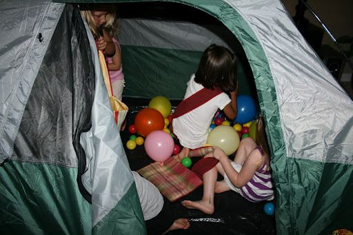 """camping party game: """"I put plastic bugs from the dollar store (7 for a dollar) on the floor of our tent and then covered them with balls and balloons. The girls had to scramble to find 5 bugs each."""""""