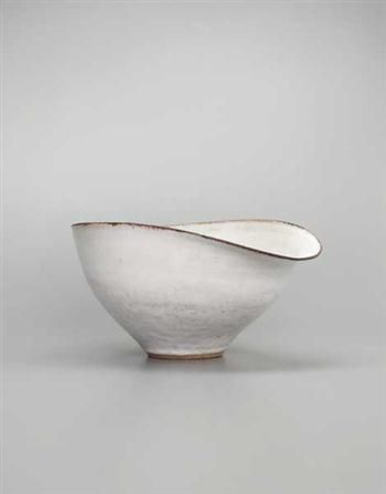 Lucie Rie Salad bowl, Stoneware, white glaze with manganese lip, mineral elements in the body creating a brown speckle, the rim formed to a pouring lip. 28 cm. (11 in.) diameter, c.1958