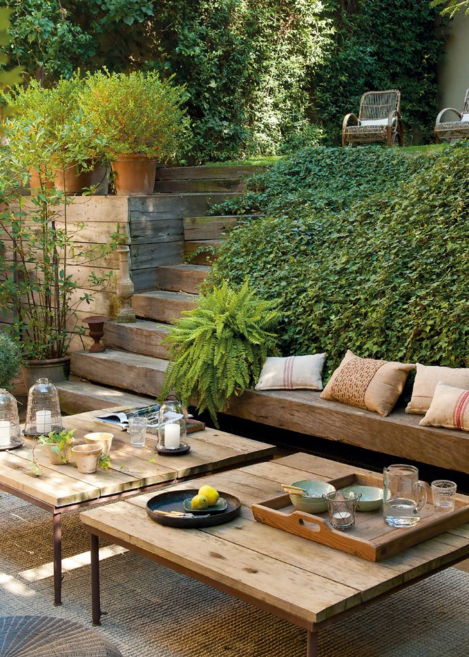 Rustic modern outdoor space most divine area with two levels. Love the bamboo type cane chairs and rustic wooden steps pallet coffee tables and rustic lanterns