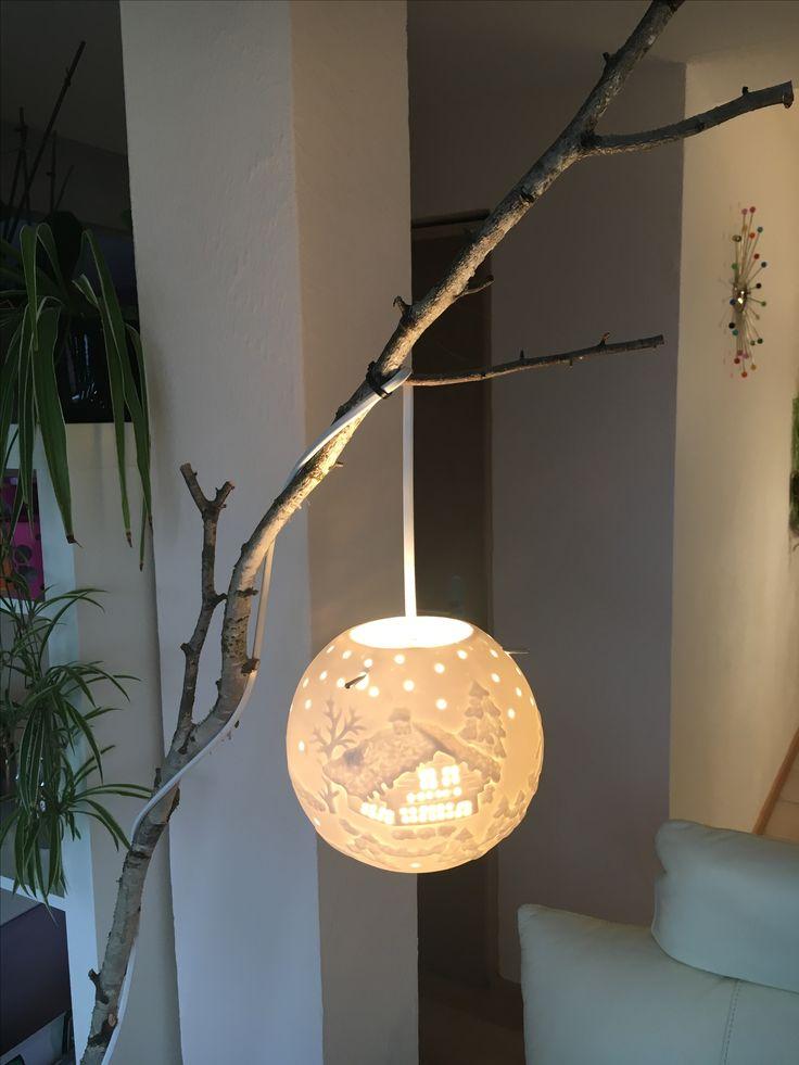 Une lampe en céramique suspendue à une branche de bouleau