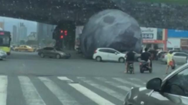 A giant model moon has rampaged through a Chinese city after being swept up by…