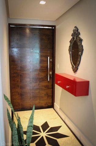 Projeto de hall de entrada com piso em mármore crema marfil e preto absoluto, móvel de vidro laqueado marsala. Parede com pintura na cor cinza de Grife (Coral) e porta de entrada pivotante em madeira. Projeto do Studio Due Arquitetura.